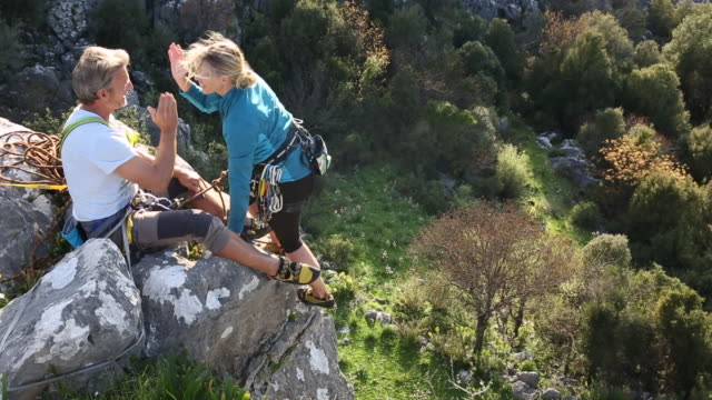 climbing couple arrive at summit, exchange high fives - republic of cyprus stock videos & royalty-free footage