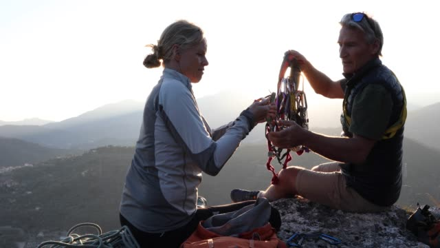 climbing couple organize gear on cliff summit - krab stock videos & royalty-free footage
