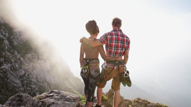 Climbing Couple standing on a ridge in the alps