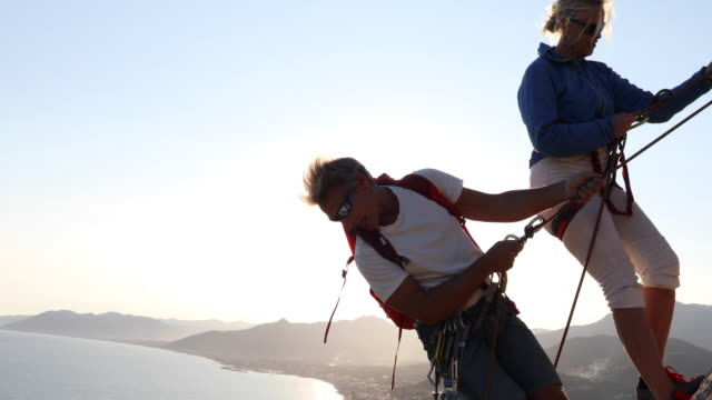 Climbing guide helps female client negotiate rappel (abseil)