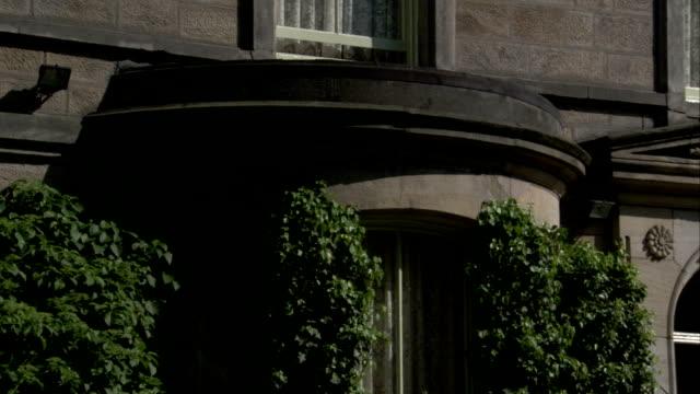 vídeos de stock, filmes e b-roll de climbing hedges frame bay windows of a stone house, leeds. available in hd. - janela saliente