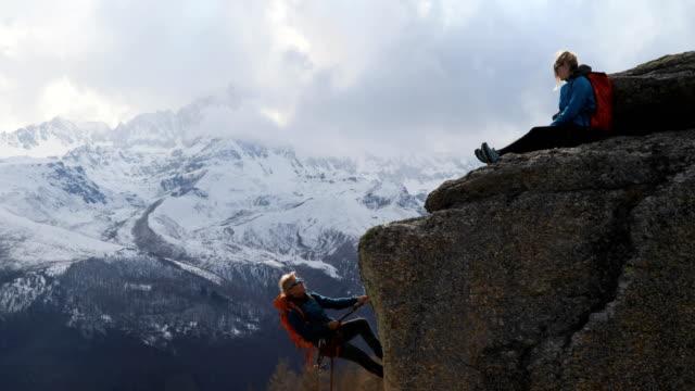 stockvideo's en b-roll-footage met klimmen instructeur leert vrouwelijke student hoe abseilen (rappel) van rocky bluff - moed