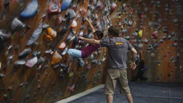 stockvideo's en b-roll-footage met climbing instructor teaching a girl on an indoor climbing wall - vrij klimmen