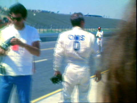 newman climbing out of porsche 914 sports coupe parked in pits at proam race ontario motor speedway / pit chief and actor james garner wearing... - white collar worker点の映像素材/bロール