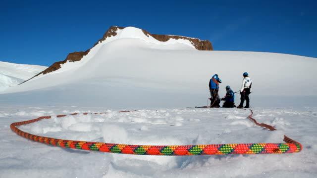 vídeos de stock, filmes e b-roll de ws climbing rope in the snow with climbers, antarctica - corda de escalada