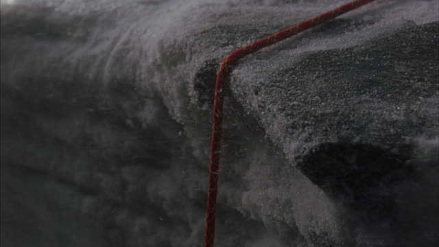 A climbing rope is pulled tight over an icy ledge and then breaks.