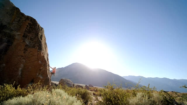 stockvideo's en b-roll-footage met climbing through - boulder rock