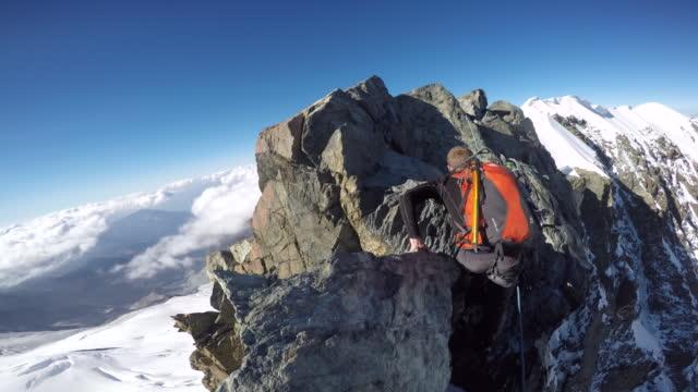 POV climbing up steep alpine ridge and cliff