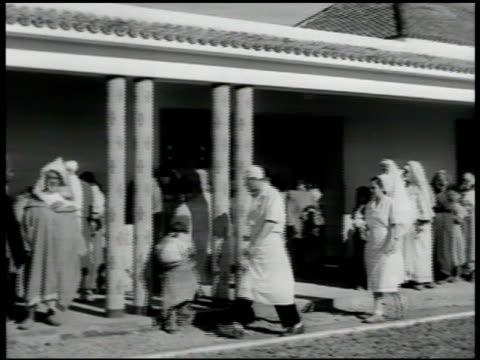 vídeos y material grabado en eventos de stock de clinic w/ moroccan people standing in line, some w/ children. moroccan male w/ swolen eye area, trachoma, eye disease. int clinic w/ doctors, nurses... - 1951