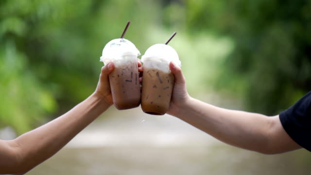 clink glasses of cold chocolate and iced coffee in nature in slow motion - hot chocolate stock videos & royalty-free footage