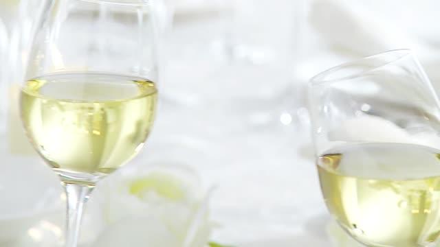 Clinking glasses of white wine