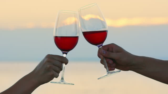 slo mo clinking red wine glasses by the sea at sunset - bicchiere da vino video stock e b–roll