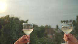 Clinking wine glasses at sunset man and woman hands only, cheers with white wine