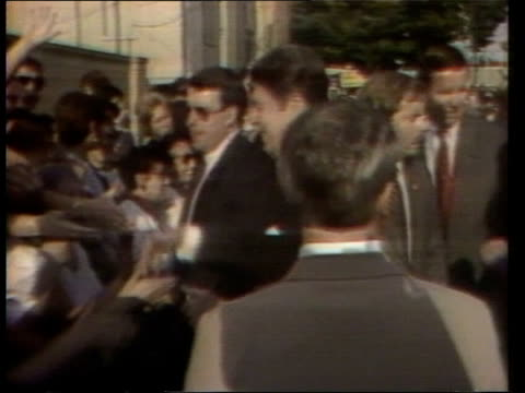 Clint Eastwood TX New Jersey Pres Ronald Reagan shaking onlookers PAN LR Frank Sinatra MS Reagan standing waving hand as standing next to Catholic...