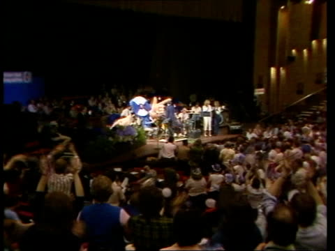 Wembley Conference Centre TLS Stage as Kenny Everett LR to front of stage MS Kenny Everett wearing large blue white rosette round neck huge hands at...
