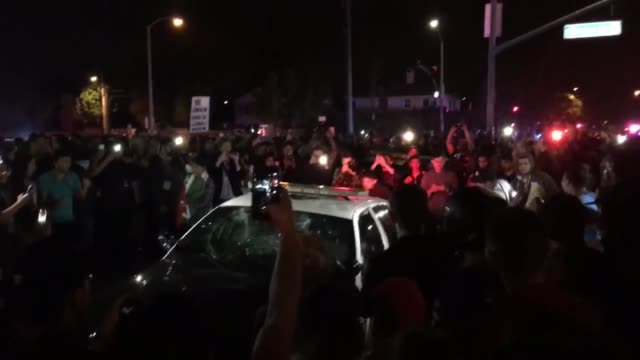 police dissiminate the protest crowds at trump rally. clip 2: protester vandalize police car at trump rally. clip 3: cop car gets stomped on at trump... - costa mesa stock videos & royalty-free footage