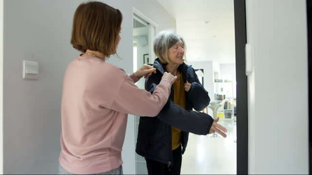 clip of an adult woman helping her senior mother put on her jacket, ready to go out - parent stock videos & royalty-free footage