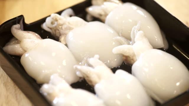 vidéos et rushes de 2 pinces de préparation des bébés crus seiche sur un plateau dans la cuisine. - seiche