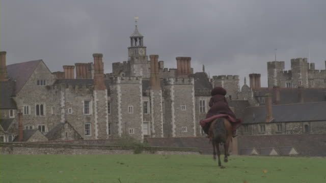 a cloaked woman rides a galloping horse toward knole house in kent. - galoppieren stock-videos und b-roll-filmmaterial