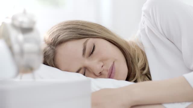 vidéos et rushes de horloge alarme réveil une femme - drap