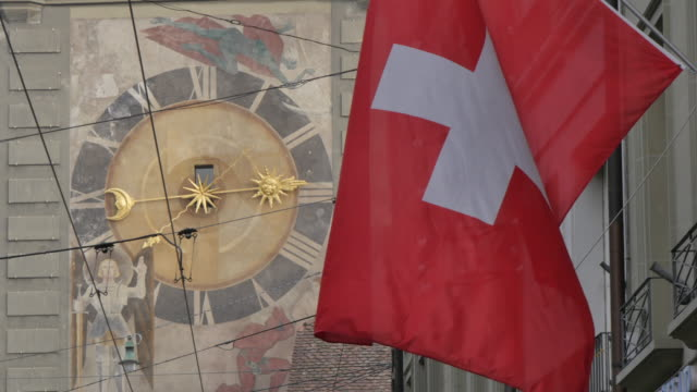 clock and swiss flag on marktgasse, bern, canton of bern, bernese oberland, swiss alps, switzerland, europe - switzerland stock videos & royalty-free footage