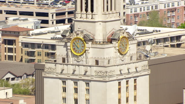 CU AERIAL ZO clock at University of Texas tower and back to reveal campus / Austin, Texas, United States