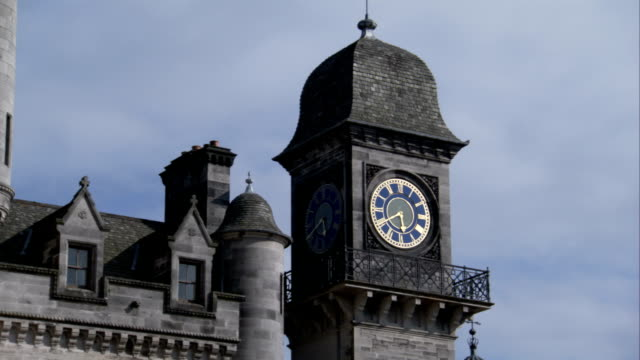 a clock face decorates a tower of dunrobin castle. available in hd. - turmuhr stock-videos und b-roll-filmmaterial