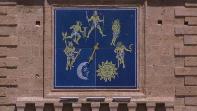 a clock face features a sun, moon, and mythical beings. - mythologie stock-videos und b-roll-filmmaterial