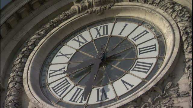 A clock keeps time on the facade of the Paris-Gare de Lyon metro station.