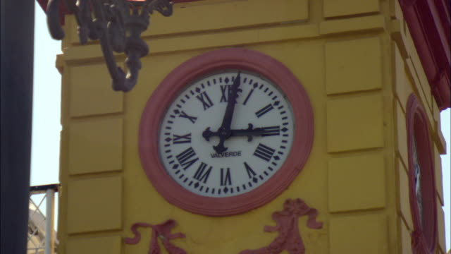 ms clock on exterior wall of yellow building / seville, andalusia, spain - romersk siffra bildbanksvideor och videomaterial från bakom kulisserna