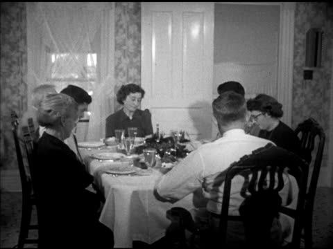 00 the Paddock family gathered around dinner table praying son Jim Paddock talking to family about service family members sitting around the table...