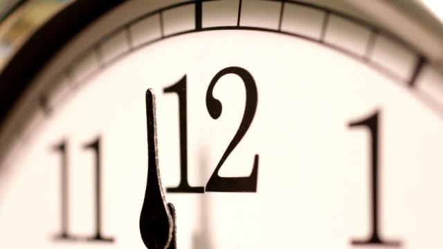 vídeos de stock, filmes e b-roll de clock passing 12 o'clock midnight. - meia noite