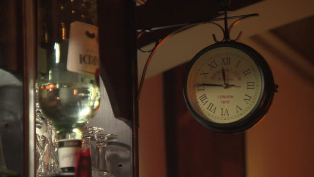 clock reading 'kensington station', 'london', '1879' shows the time quarter to twelve in a continental bar. - roman numeral stock videos & royalty-free footage
