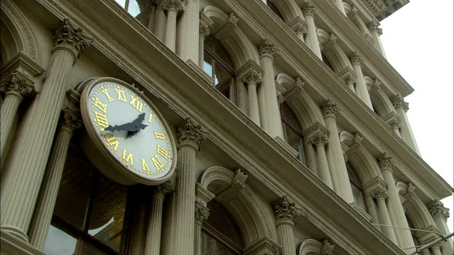 a clock reads 12:43 on the exterior of a new york city high rise. - architectural column stock videos & royalty-free footage
