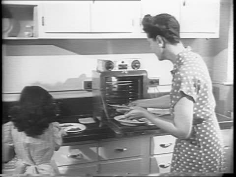 mother pulls out pre-made meals from the oven and serves them to her family for dinner / family at table eating dinner / man takes bite from fork /... - slit och släng bildbanksvideor och videomaterial från bakom kulisserna