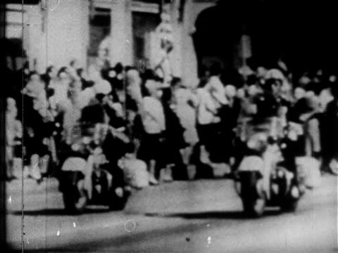 stockvideo's en b-roll-footage met 25 pm vs motorcade escorting presidential limousine w/ jfk wife jacqueline kennedy texas governor john connally wife nellie through dealey plaza tx - jacqueline kennedy