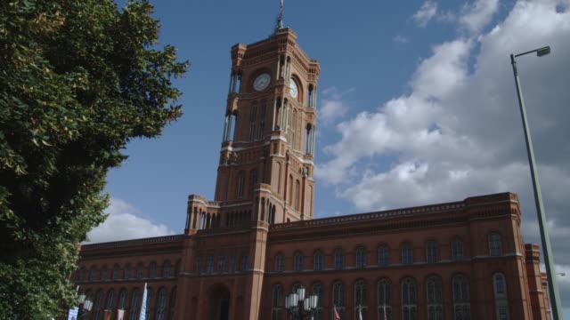 a clock tower dominates the rotes rathaus in berlin, germany. - rathaus bildbanksvideor och videomaterial från bakom kulisserna