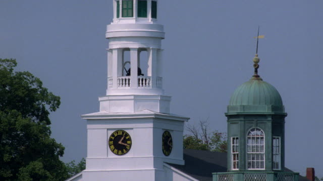 a clock tower features a white steeple. - steeple stock videos & royalty-free footage