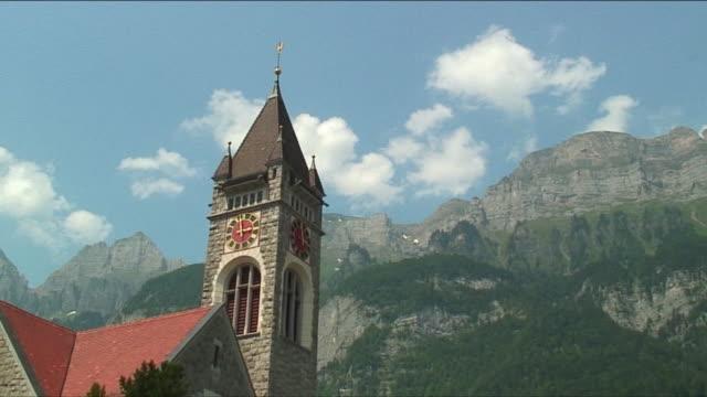 ws la pan clock tower in front of mountain in swiss alps / near zurich, switzerland - 尖り屋根点の映像素材/bロール