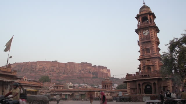 clock tower in the sardar market with mehrangarh fort in the background, jodhpur, india - sweeping stock videos & royalty-free footage
