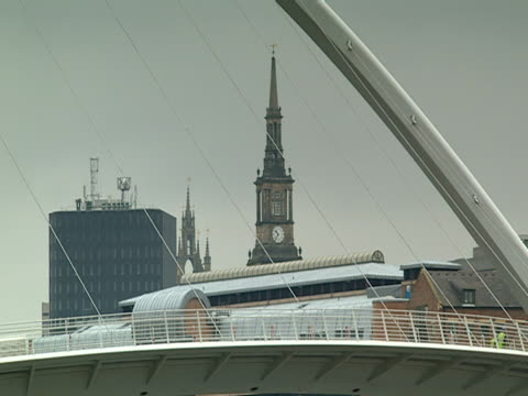 a clock tower is seen under a support beam of the gateshead millennium bridge. - tyne and wear stock videos & royalty-free footage