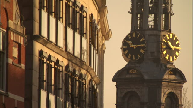 a clock tower keeps time in amsterdam. - turmuhr stock-videos und b-roll-filmmaterial