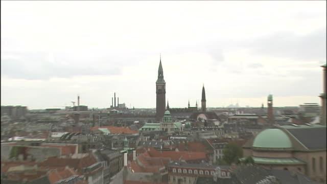 a clock tower looms over copenhagen. - 宗教上のシンボル点の映像素材/bロール