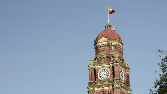 ms la clock tower of colonial high court building with myanmar flag / yangon, yangon division, myanmar - clock tower stock videos and b-roll footage