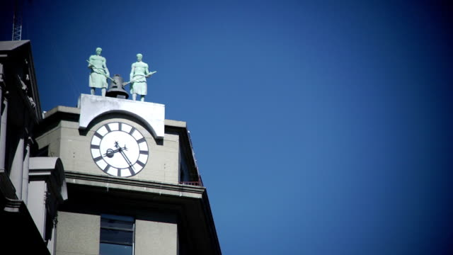 clock tower w/ two human figure statues standing on top, clear blue sky bg. - human face video stock e b–roll