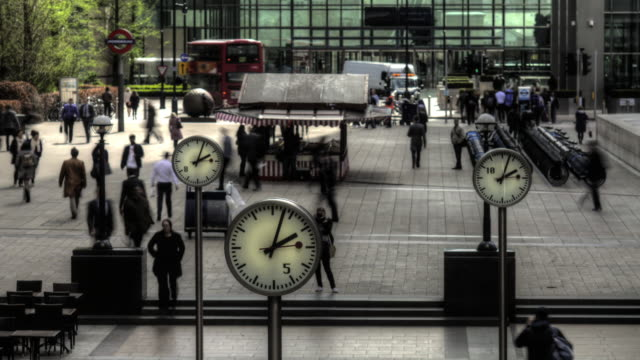 clocks depict time passing at canary wharf, london. - clock stock videos and b-roll footage