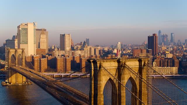 ausderatonansicht des brooklyn bridge towers mit der fliegenden amerikanischen flagge oben, mit der fernen ansicht der skyline von manhattan über den east river im hintergrund. drohnenvideo mit der statischen kamera. - brooklyn bridge stock-videos und b-roll-filmmaterial