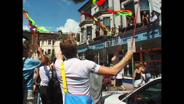 close and medium views of people parading as part of pride, including view of people dancing and waving multi-coloured ribbons cheered on by others... - hanging stock videos & royalty-free footage