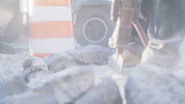 close angel of construction workers using jackhammer on concrete. construction worker. wheelbarrows, shovels, and boots visible. - wheelbarrow stock videos and b-roll footage