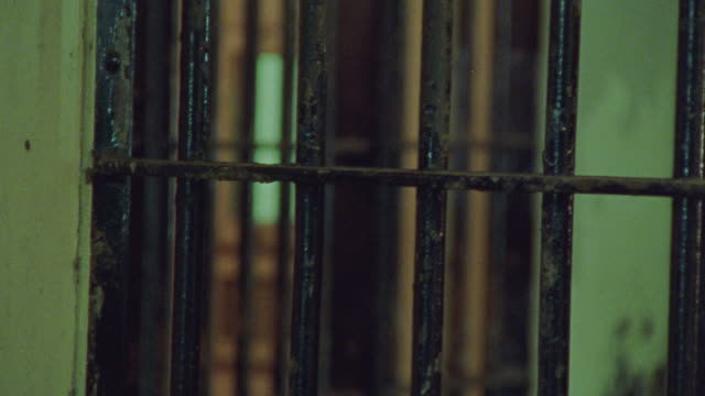 close angle. looking out from inside jail cell. probably at police station. switches from focus on bars in fg to bars in bg. - security screen stock videos & royalty-free footage